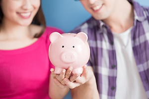 Couple holding up piggy bank