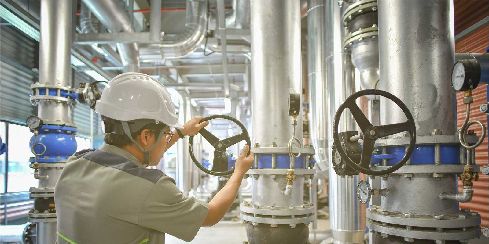 water treatment plant worker rotating a pipe wheel.jpg