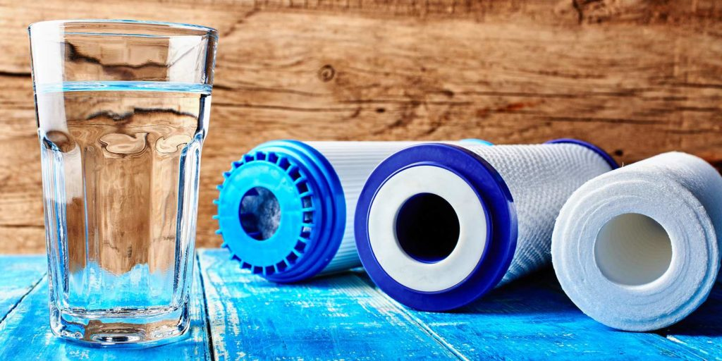 Cartridge water filtration, a type of physical filtration solution and a glass of water on a wooden background