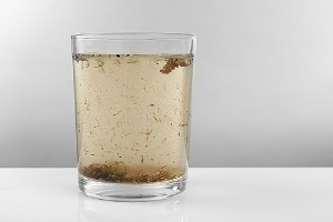Glass of contaminated water. Bag filtration is an effective water filtering solution
