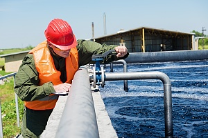 cooling tower water treatment expert treating some water at a facility with an orange work vest