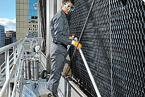cooling tower water technician cleaning a glycol cooling system on outside building