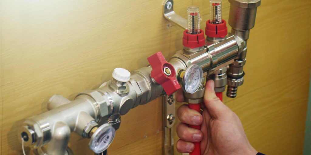 plumber checks the temperature of the pipes after applying glycol to the piping system