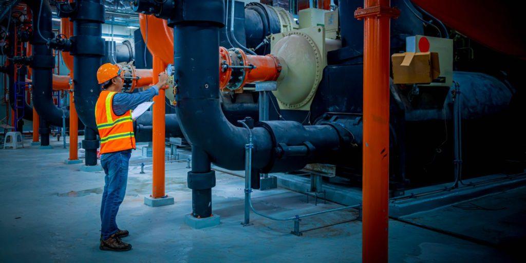 Expert conducting routine checkup on HVAC water treatment machineries