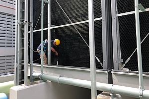 a commercial building owner cleaning a cooling tower on the top of his building