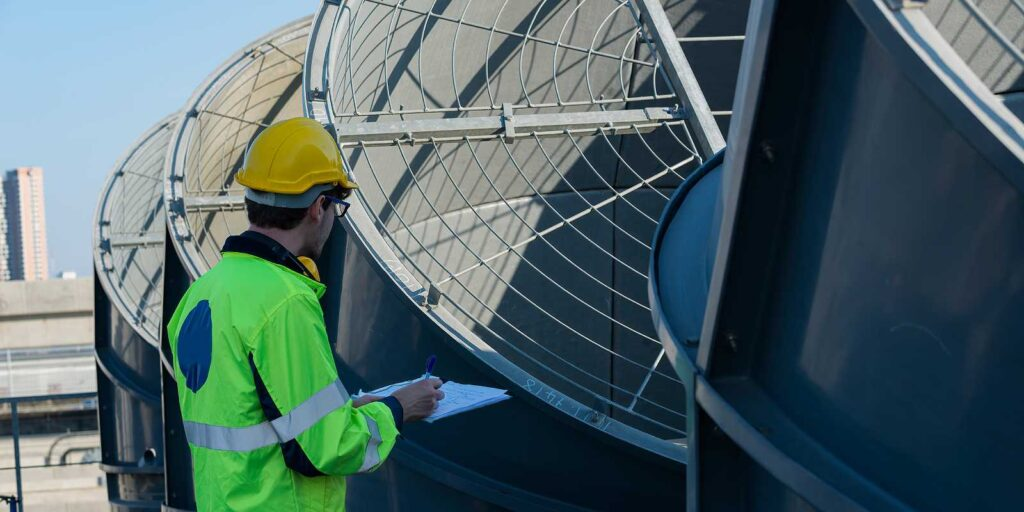 Worker holding checklist conducting routine maintenance checkup