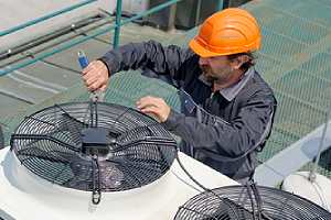 Repairman on the roof fixing huge cooling tower system