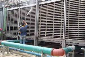 Worker conducting routine cooling tower cleaning