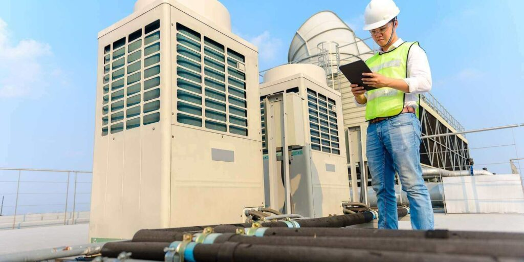 engineer holding tablet is checking the cooling tower