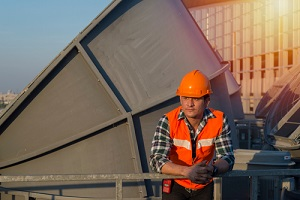 worker checking motor of cooling tower on top