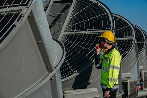 worker on cooling tower on blue sky background